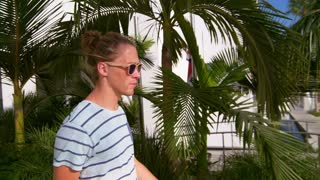 Handsome man walking along tropical city with palm trees in slow motion. Stylish guy walking along tropical town with palm trees. Hipster in sunglasses going near palm leaves
