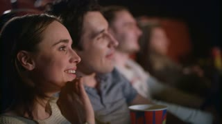 Happy couple watching comedy in cinema. Woman smiling at comedy movie session. Cinema people watching film in slow motion. Joyful people enjoy movie entertainment. Friends enjoy movie