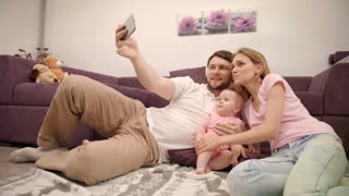 Happy family making selfie at home. Young family with little baby take a picture on mobile phone. Happy togetherness life concept. Father take photo with wife and daughter. Enjoy life