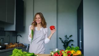 Happy girl dancing and singing in kitchen with cucumber as microphone. Cheerful girl dancing expressive with fresh vegetables. Singing woman having fun and cooking healthy food