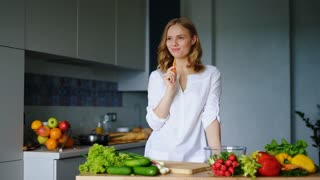 Happy girl eating carrot in kitchen. Healthy woman with fresh spring vegetables. Natural ingredients for salad. Smiling pretty girl in white shirt in kitchen. Vegetarian food cooking. Healthy eating