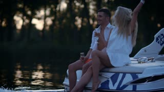 Happy lovers boating on river in evening. Young stylish couple in love have fun outdoor. Love couple enjoy walk on water at night