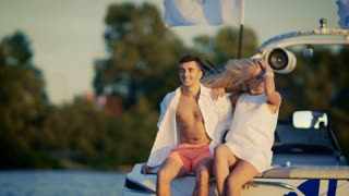 Happy married couple in love resting together on yacht. Romantic summer vacation on water. Smiling lovely couple enjoying outdoors at sunset. Happy people relaxing on yacht