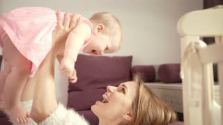 Happy mom with child. Beautiful woman holding baby on hands. Sweet baby time. Female happy life concept. Mother enjoy baby laughing. Happy mother holding her baby at home