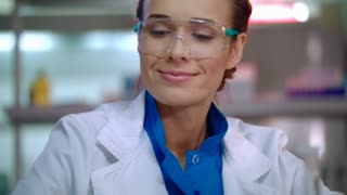 Happy researcher in lab. Lab researcher in safety glasses. Woman scientist face. Lab technician smiling. Female lab scientist smiling. Happy woman scientist in laboratory. Female researcher portrait