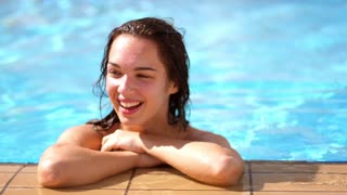 Happy woman face in swimming pool. Close up of woman portrait smiling in resort pool water. Happy female face. Woman relax in water. Enjoy summer vacation. Holiday lifestyle