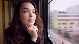 Happy woman face looking train window. Close up of smiling woman traveling by train. Happy traveler in train. Female tourist enjoy railway road