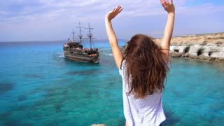 Happy woman on seashore rejoicing arrival of sailing ship into bay. Brunette girl waving arms to old ship in sea. Woman giving signals to old sailing ship in slow motion