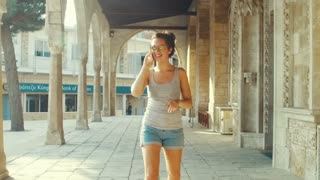 Happy woman speaking on mobile phone. Smiling pretty girl in sunglasses walking on street with ancient architecture. Summer vacation in Cyprus city. Attractive tourist talking on phone in old city