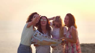Happy woman tourist looking route map. Group of woman discussing travel route. Traveling people find route. Travel friends laughing at sunset beach. Female tourist trip