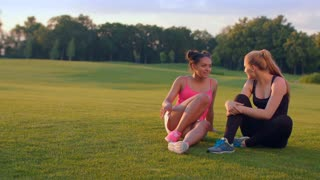 Happy women sitting on grass in summer park. DIverse friends talking outdoors. Multi ethnic girls talking on meadow. Mulatto woman talking with blonde woman. Sport woman talking after training