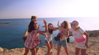 Happy young people have fun on rocky cliff. Cheerful young tourists greet each other in slow motion. Happy friendship concept. Happy youth at sea coast. Young friends enjoy summertime