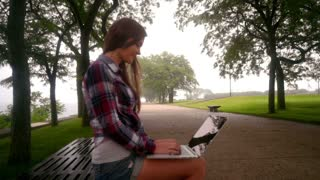 Happy young woman with laptop sitting on bench in park. Side view of woman using laptop outside. Remote working concept. Beautiful woman typing on laptop in empty park. Woman working laptop