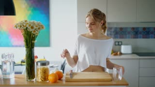 Healthy woman cutting orange on wooden board. Preparing morning breakfast in modern kitchen. Cutting orange fruit for squeezing fresh juice process. Woman healthy lifestyle with natural food