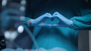 Heart surgery concept. Close up of surgeon showing heart hands at surgeon room. Safe life. Heath care industry. Medical hands show heart