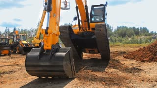 Heavy caterpillar excavator working on construction site. Orange excavator bucket work in quarry. Big powerful construction machine with excavator bucket. Earth moving equipment working