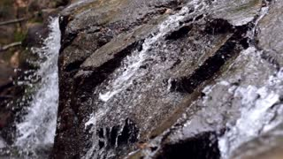 Hidden waterfall in wet rock. Clear indescent water quickly flow downhill in rocky mountain. Close-up of flowing water on stone
