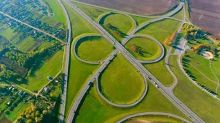 Highway interchange aerial view. View from above beautiful landscape intersection road. Aerial view highway junction. Road junction. Cars traffic on highway intersection. Interchange highway road