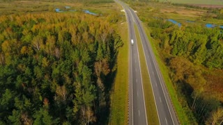 Highway road in forest landscape. Aerial view of cars driving on asphalt road between trees. Drone view of highway in forest. Cars moving on country road. Highway road in forest. View from above