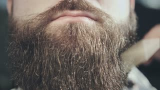 Hipster man beard care. Man beard style. Close up of combing hair beard on face hipster. Bearded hipster face. Hipster moustache lips. Moustache man face. Moustache close up. Barber comb