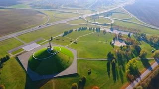 Historical monument on highway intersection. Aerial landscape city monuments. Aerial view of cars driving at highway junction. Past memorial. Beautiful landscape cars traffic on freeway interchange