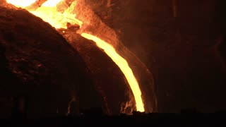 Hot metal pout out from blast furnace. Liquid metal pouring from blast furnace. Molten metal pouring from industrial furnace. Liquid steel falling from blast furnace. Liquid iron flow