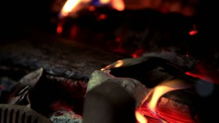 Hot red coals lie in bonfire. Firewood burns in red flames fire. Close up of smoldering red coal against background of burning flames of fire. Burning firewood in fire of red bonfire