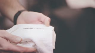 Hot towel in male hands. Warm towel in barber man hand. Hot towel shave. Close up of white towel spa steaming. Spa services. Hot shave. Barber shop tools