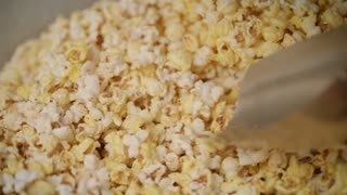 Human hand pouring ready popcorn from popcorn machine by ladle. Process of popcorn production. Selling fresh pop corn in movie theatre. Machine for production of corn. Food cinema background