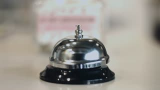 Human hand ringing silver service bell on hotel reception desk. Close up hotel accommodation call bell or reception sign. Metallic concierge ring on desk in lobby. Hospitality services concept