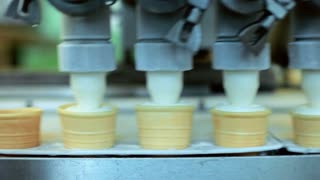 Ice cream pouring in waffle cones. Automated production line at food factory. Ice cream machine. Ice cream production line. Ice cream manufacturing process. Food industry. Food processing plant