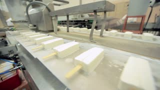 Ice cream production line. Food factory. Food processing plant. Vanilla ice cream manufacturing line at industrial workshop. Sweet food conveyor line. Food industry. Ice cream manufacturing process
