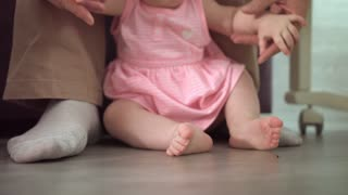 Infant feet learning walk. Close up of baby first step with father support. Daddy learning walk little baby. Little steps at home. Parent support concept. Baby feet walking on floor