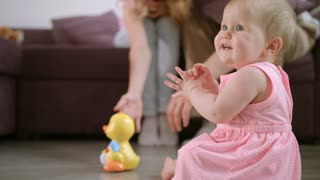 Infant playing with toy on floor. Adorable baby crawling on floor at home. Cute child girl in pink dress playing at home. Sweet baby enjoy walking in room. Beautiful girl crawl with on floor