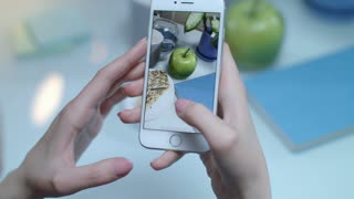 Instagram food concept. Close up of female taking mobile video of green apple. Smart phone video of healthy food. Culinary video on smartphone. Hand holding mobile and shooting apple and snacks