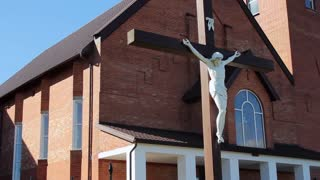Jesus on cross. Modern catholic church. Close up of crucifixion of Jesus Christ. Church building exterior. Religion and saint faith concepts
