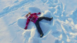 Kid making snow angel. Young cheerful girl lying on snow. Winter child fun. Beautiful girl playing in snow