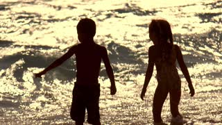 Kids silhouette on sunset waves background. Little boy and girl enjoy sunset waves. Little boy showing finger on sunset water wave. Summer childhood concept