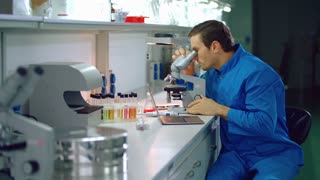 Lab doctor looking microscope. Laboratory doctor using laptop in medical lab. Medical researcher looking through microscope. Clinical laboratory research. Lab worker using medical microscope