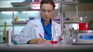 Lab doctor writing clinical data research. Clinical research in medical lab. Woman lab writing medical research report. Medical researcher writing research results