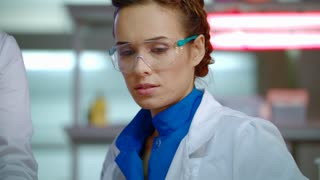 Lab researcher in laboratory. Close up of female scientist in safety glasses. Medical researcher sitting in clinical lab. Portrait of lab woman working in research lab. Woman scientist face