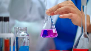 Lab scientist pouring liquid in lab flask. Close up of female scientist doing laboratory experiment. Lab worker hands doing laboratory testing with chemical liquid in beaker