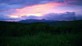 Landscape with evening mountains. Majestic sunset in mountains landscape. Pink sunset with evening clouds above hills. Time-lapse of dusk in mountains. Evening sunset with clouds