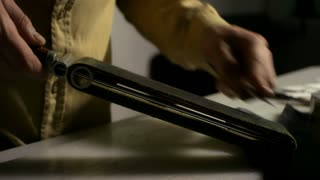Leather maker sharpening stencil knife with whetstone. Close up man hands sharpening blade of knife. Man stropping knife with leather strop at home workshop. Cutting tool for leather manufacturing