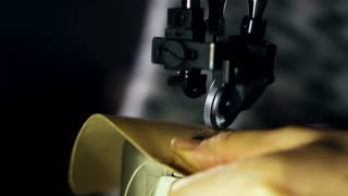 Leather sewing machine in action in workshop. Close up craftsman hands stitching leather material. Artisan stitching leather parts. Leather stitching professional equipment. Handmade tailoring process