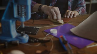 Leather worker polishing finished product. Leather manufacturer working with product in home workshop. Final processing leather goods at craft workshop