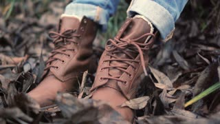 Legs in brown shoes with laces front view. Close up legs in jeans and boots standing on fallen autumn leaves in forest