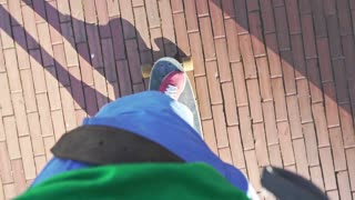 Legs ride on skateboard. Hipster lifestyle concept. POV of woman riding on longboard on city streets. Close up of female teenager skateboarding outdoors