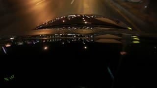 Light reflections on car glass and car hood at night. Roof and hood of moving auto in night city. Bright road lights on car at night. Night driving