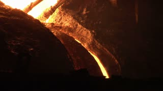 Liquid iron pouring from blast furnace. Close up of blast furnace working. Iron and steel production. Iron melting in blast furnace. Molten iron production. Electrodes in blast furnace
